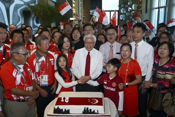Singapore's President Tony Tan and guests cheer as they prepare to cut a cake during the Singapore National Day Reception in Rio de Janeiro