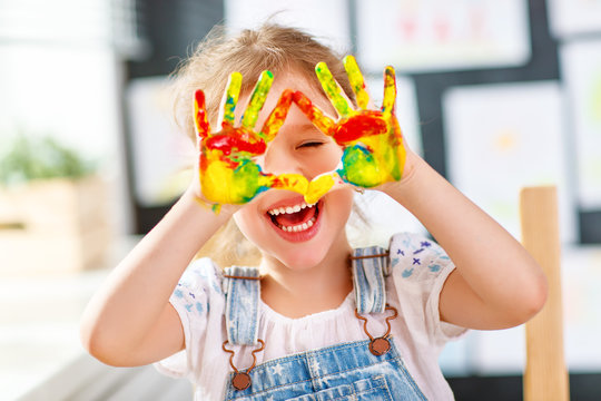 funny child girl draws laughing shows hands dirty with paint