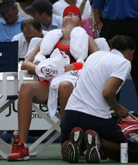 Mladenovic of France sits with an ice-filled towel on her shoulders as she tries to cool off between games during her quarterfinals match against Vinci of Italy at the U.S. Open Championships tennis tournament in New York