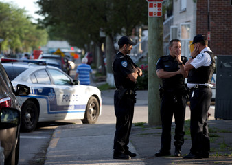Police investigators talk outside the home of Amor Ftouhi, in Montreal