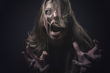 Crazy deranged woman pulling her hair out, scary and insane, halloween concept, possessed by evil spirits