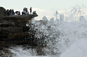 Spectators watch from a clifftop as they watch competition in heavy seas during the Cape Fear surfing tournament off Sydney's Cape Solander in Australia