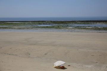A man uses a sun umbrella on Petit Sergent beach in Le Bois de Plage en Re