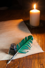 Quill pen, inkwell and a letter by candle light