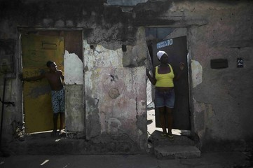 Neighbors of Rafaela Silva stand outside her house in the Cidade de Deus slum