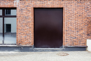 closed metal doorway painted brown on red brick wall backgrounds