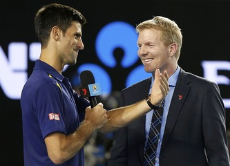 Serbia's Djokovic takes the microphone from former tennis player Courier while being interviewed after winning his semi-final match against Switzerland's Federer at the Australian Open tennis tournament at Melbourne Park