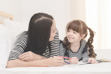 Happy family in the bedroom,Asian mother teaching her daughter child to learning for  preschool. Photo design for family, children and happy people concept.