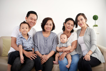 Portrait of big Asian family posing for photo at home, all smiling happily looking at camera