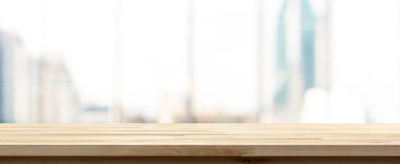 Wood table top on blur  city building view background looking through glass window, panoramic banner