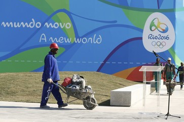 A construction worker walks by a microphone where IOC President Bach is awaited to hold a speech in Rio de Janeiro