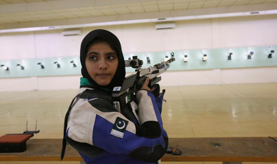Minhal Sohail looks back as she prepares to shoot her air rifle during a practice session at the Pakistan Navy Shooting Range in Karachi