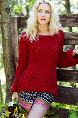The beautiful, happy woman outdoors in a red sweater