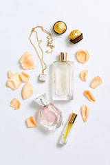 Perfume bottles with flowers petals on white background. Perfumery, cosmetics, jewelry and fragrance collection. Stylized feminine flatlay. Women accessories top view.