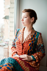 Girl with retro hairstyle in ethnic dress sits by the window