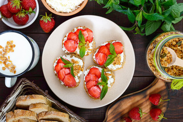 Mini sandwiches with cottage cheese, fresh strawberries, decorated with mint leaves on rye bread on a dark wooden background. Top view. Proper nutrition. Healthy food. Dietary menu.