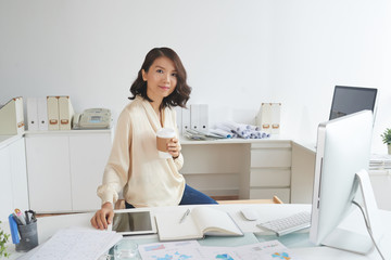 Portrait of beautiful Asian secretary posing at workplace with paper coffee cup