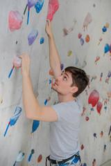 A successful man climbing on climbing wall. Teenage rock climber on boulders.