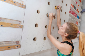 Woman climbing on climbing wall. Teenage rock climber in sportswear and equipment.
