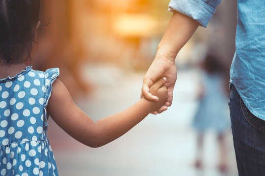 Mother and daughter holding hand together in vintage color tone