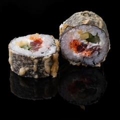 Sushi served on a black background with reflection.