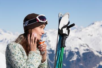 femme à la neige qui met de la crème  solaire sur son visage