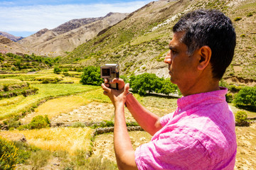 Closeup of a tourist filming and taking photos of a valley in the Atlas mountains.