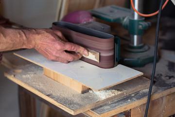 Carpenter's Hand using electric sander tool
