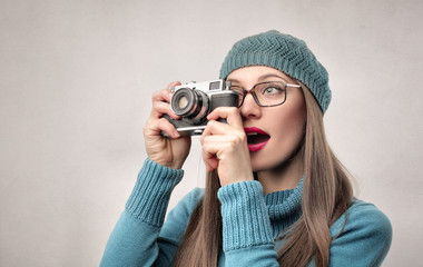 Pretty girl making a picture with a vintage camera