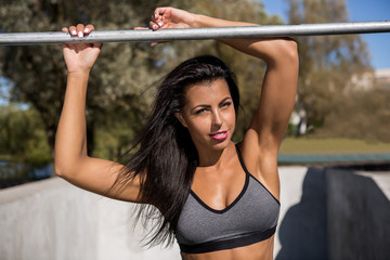 Beautiful young woman in sexy outfit with pretty athlete muscular body rest near crossbar after hard workout. Crossfit training urban area street gym city exercise routine healthy lifestyle.