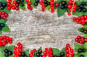 Fruits frame with berries fresh currants on wooden background wi