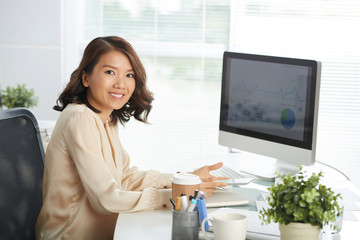 Portrait of young Asian businesswoman smiling at camera while sitting at computer desk with digital tablet in her hands