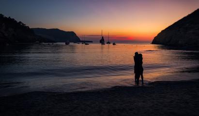 Ibiza, España, Cala de Benirrás. Puesta de sol . Siluetas de enamorados, barcos e islotes al fondo