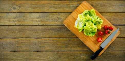 Lettuce and tomatoes on wooden cutting board