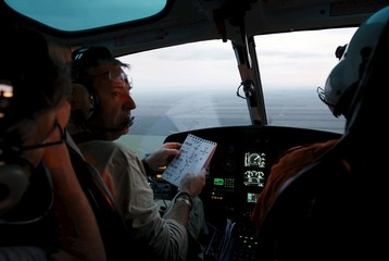 Lavigne talks to the helicopter pilot as he checks on the roads of the Termas de Rio Hondo-Jujuy third stage in the Dakar Rally 2016 in Santiago del Estero province