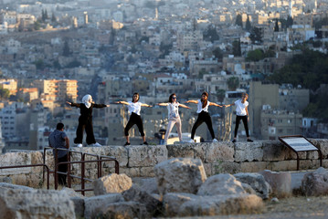 Yogis and tourists take pictures after their yoga practice in celebration of International Day of Yoga at Amman Citadel
