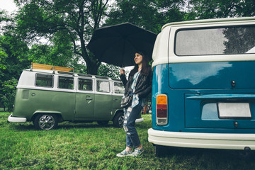 woman staing near retro van with umbrella
