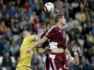 Czech Republic's Skoda is sandwiched as he fights for the ball with Latvia's goalkeeper Vanins, Gorkss and Dubra during their Euro 2016 group A qualification match at the Skonto stadium in Riga