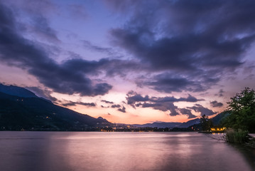 Dramatic sunset cloudscape over mountain lake, cold and warm gradient