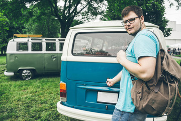 man wants to put his bag into tunk of his van