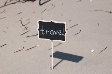 Black wooden board with inscription travel on the seashore