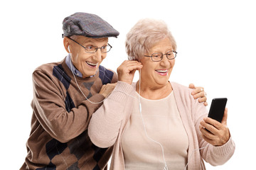Elderly couple listening to music on a phone together