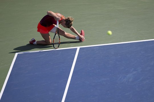 Halep of Romania stretches a leg muscle after losing a point to Lisicki of Germany during their fourth round match at the U.S. Open Championships tennis tournament in New York