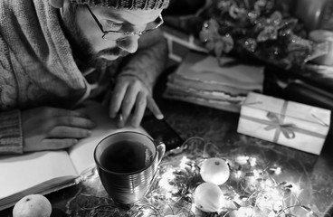 monochrome photo of man with a blank book in his hands for the New Year's table with decorations