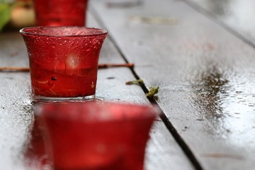 Candle glass holder red color wet and dirty on wood floor