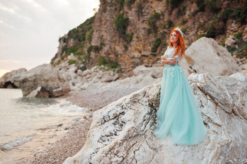 Young beautiful red-haired woman in a luxurious dress stands on a rocky shore of the Adriatic Sea among large stones