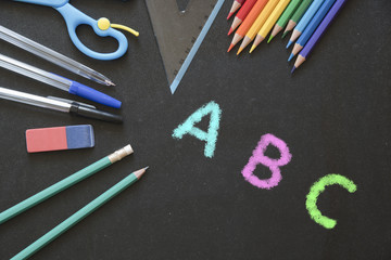 Different kinds of School and Office Utensils on a Chalkboard Surface with Colorful Letters written with Chalk