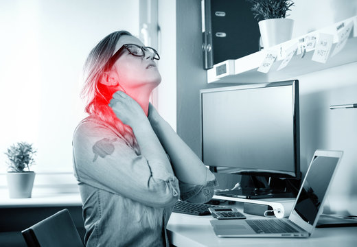 Woman in home office suffering from neck pain sitting at desk