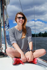 Pretty woman sits on a yacht and smiles, against the blue sky