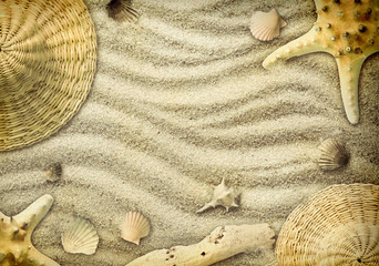Starfish, straw hat and shells on the sand